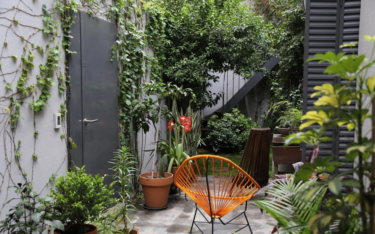 Arquitectura Reforma PH, patio exterior paisajismo minimo y celosías antiguas negras con silla de cable naranja y negra